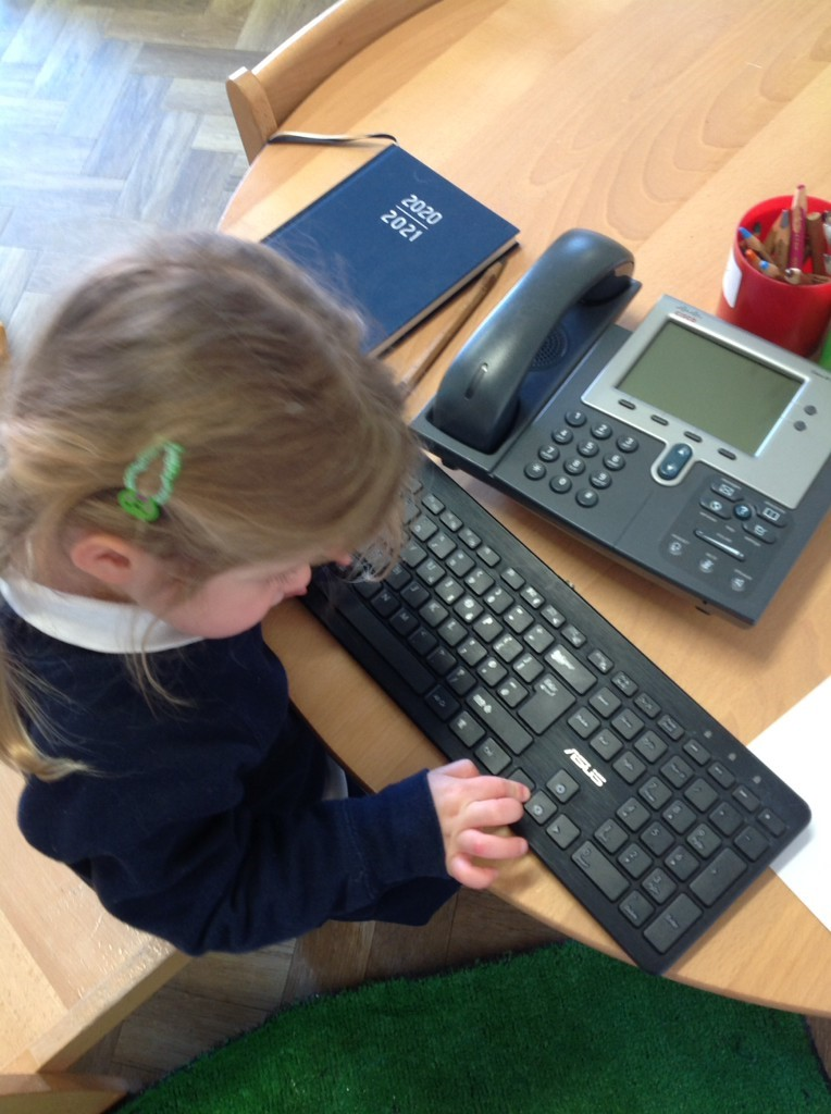 Nursery pupil on a keyboard and phone