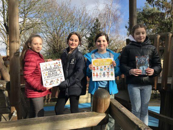 Girls holding donated books