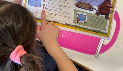 Girl reading the recipe for gruffalo crumble