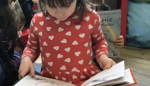 Reception girl reading book
