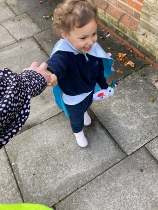 Young pupil on a walk, holding a teacher's hand