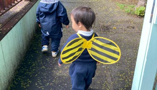 Young boy and girl walking to their nursery classroom. The girl is wearing bee wings