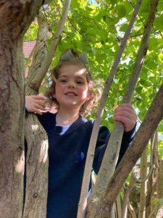 Young Peregrines Nursery pupil smiling in the trees