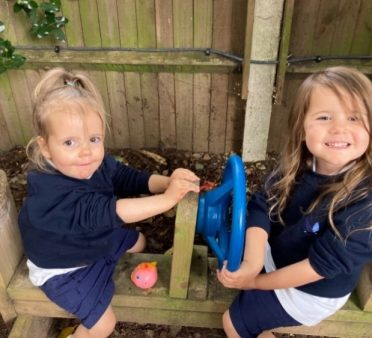 Two Peregrines Nursery girls sitting on a bench with steering wheels in the Forest School