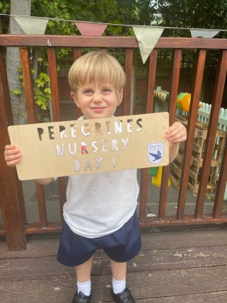 Young Peregrines Nursery boy with a sign that reads Peregrines Nursery Day 1