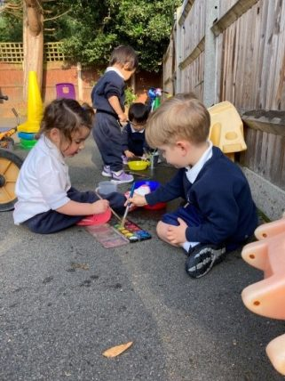 Young Peregrines Nursery children sitting down to draw on the playground floor