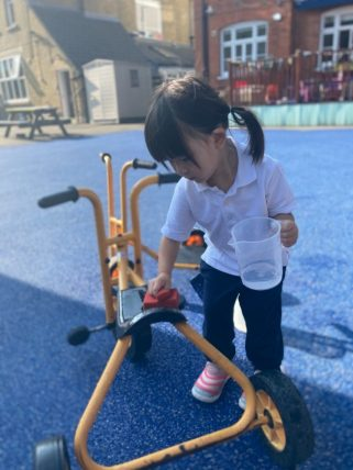 Peregrines Nursery girl playing with bike in playground